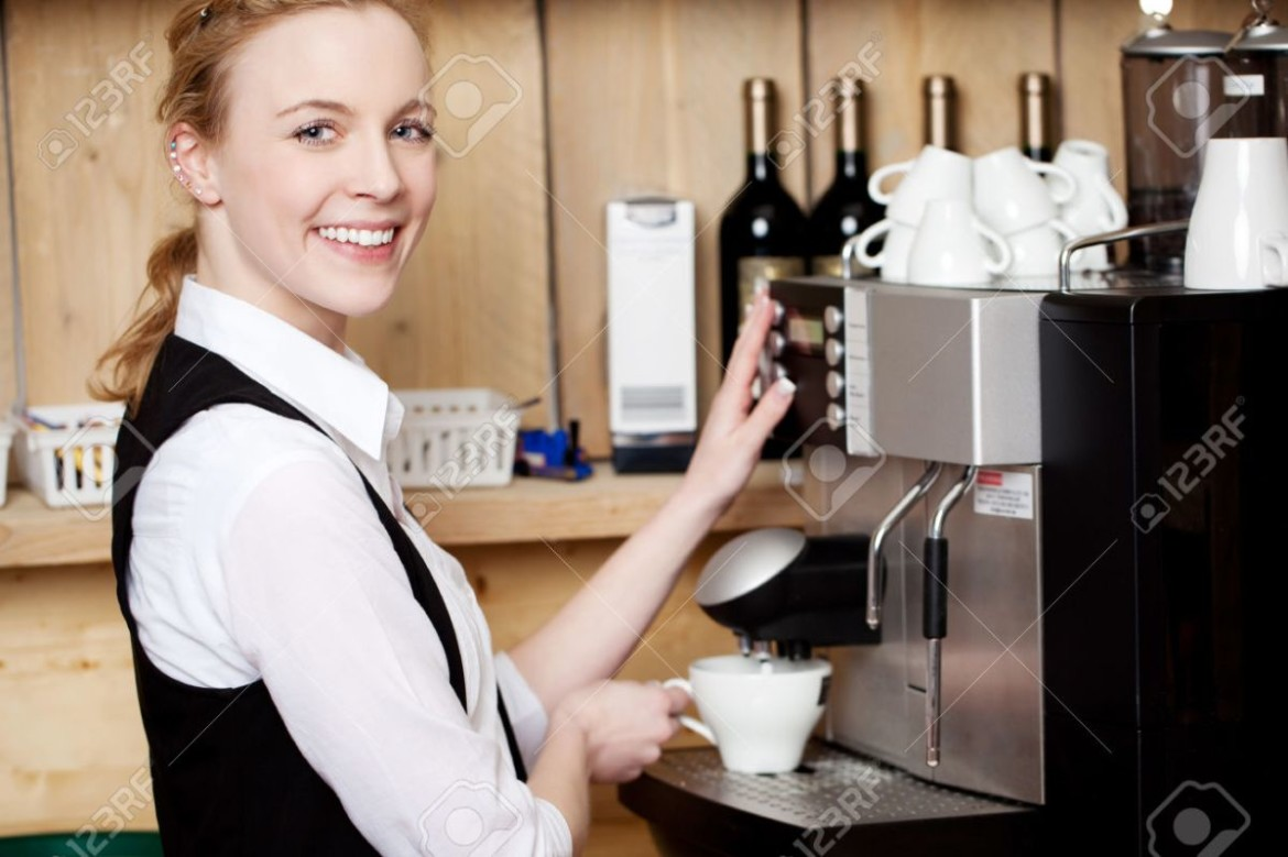 Portrait of happy young waitress filling coffee in cup from machine at cafe